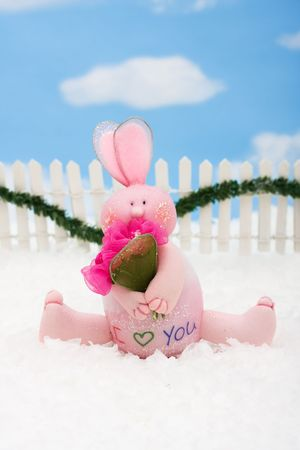 A pink bunny on a white picket fence with garland on a  sky background, Pink Bunny photo