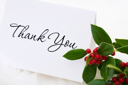 A thank you card with holly and berries on a white fur background, thank you card Stock Photo