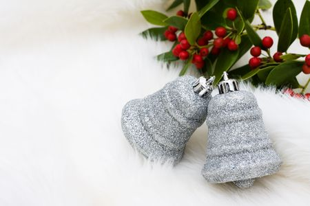 Silver bells and holly and berries on a white fur background, Christmas ornaments Фото со стока