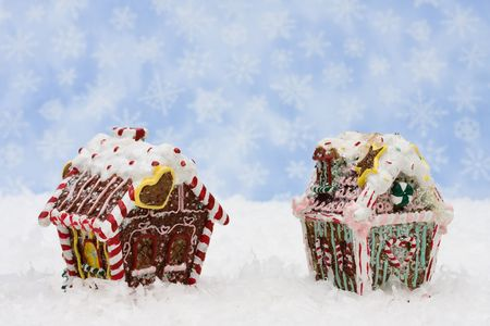 Gingerbread houses with a white fence and green garland on a snowflake background, gingerbread houses photo