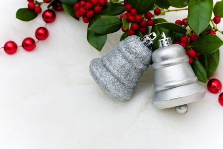 silver bells: Silver bells and holly and berries on a white fur background, Christmas bells Stock Photo