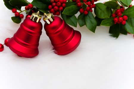 Red bells and holly and berries on a white fur background Stock Photo - 5982891