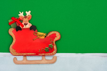 Santas sleigh with a reindeer inside and a white ribbon border on a red background photo