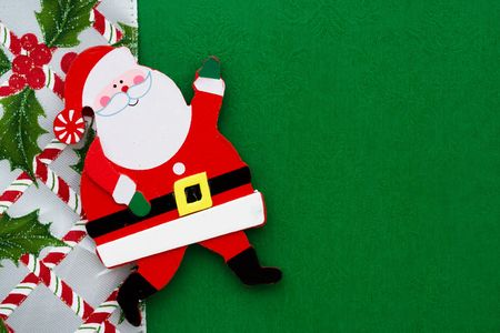 A santa claus on a green background with a candy cane  ribbon photo