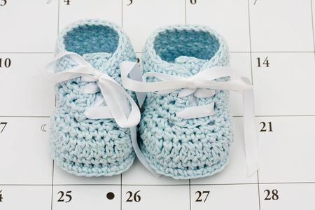 due date: Blue baby booties on a calendar background, baby due date