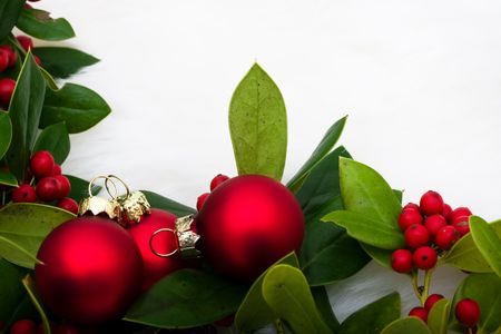 Red glass balls with holly and berries on a white fur background, Christmas balls photo