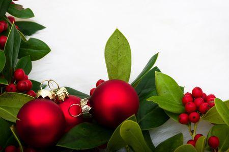 Rood glas ballen met hulst en bessen op de achtergrond van een witte vacht, Kerst ballen