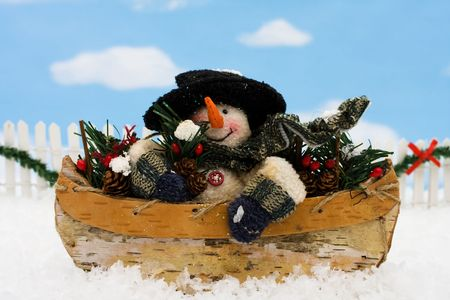 A Snowman sitting in a wooden bowl on a blue snowflake background, winter scene photo