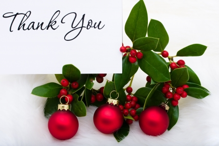 Red glass balls with a thank you card and holly and berries on a white fur background, Christmas balls Stock Photo