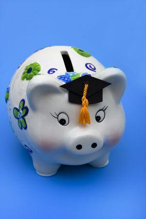 Ein hübsches Sparschwein tragen Graduation Cap auf blauem Hintergrund, Bildung Einsparungen Standard-Bild - 6123920