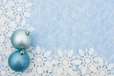 Snowflakes making a border with christmas balls on a blue background Stock Photo