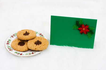 A plate of cookies with a blank card on a white fur background photo