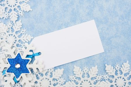 Snowflakes making a border with a blank gift tag on a blue background photo