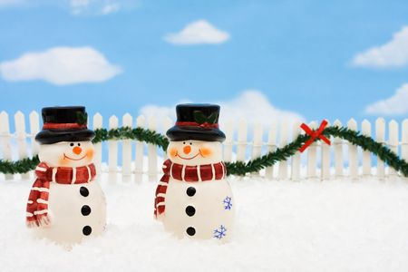 picket fence: A snowman on a white picket fence with garland on a  sky background