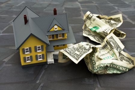 Yellow model house with crumpled dollar bills sitting on a dark background, yellow house photo