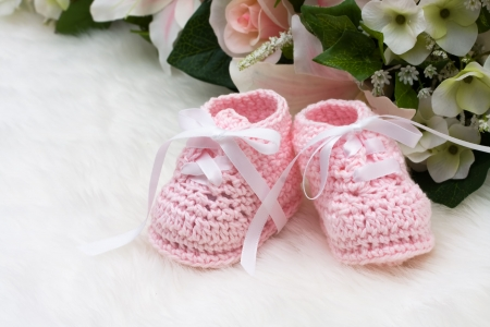 Baby booties with flowers sitting on a white background Stock Photo - 6269806