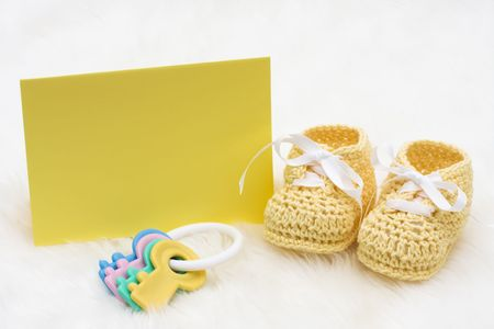 teether: Baby booties with a blank card sitting on a white background