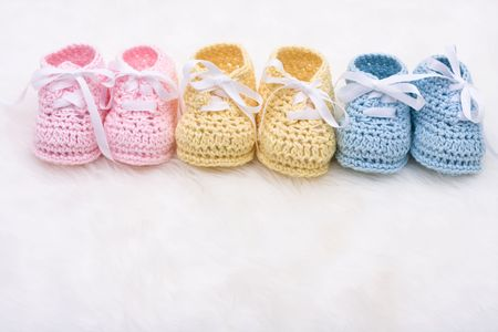 Three pairs of baby booties on a white background Reklamní fotografie