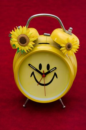 smiley: A yellow retro smiley face clock on a red background, smiley clock Stock Photo