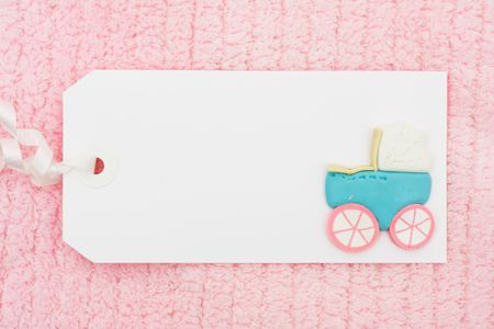 A blank gift tag with a baby stroller on it with a pink background Stock Photo