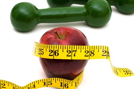 A measuring tape wrapped around an apple with hand weights Stock Photo - 6278679