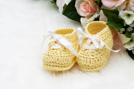 Yellow baby booties with flowers on a white background