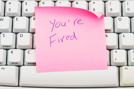 A pink sticky note sitting on a computer keyboard, You are fired photo