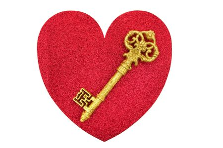 A gold key on a red heart on a white background, key to my heart photo
