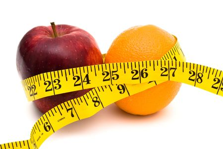 An apple and an orange with a measuring tape on a white background, healthy living photo