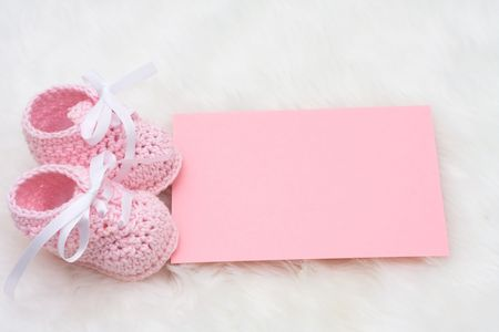 Baby booties with a blank card sitting on a white background