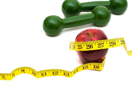 A measuring tape wrapped around an apple with hand weights, healthy eating Stock Photo - 6307873