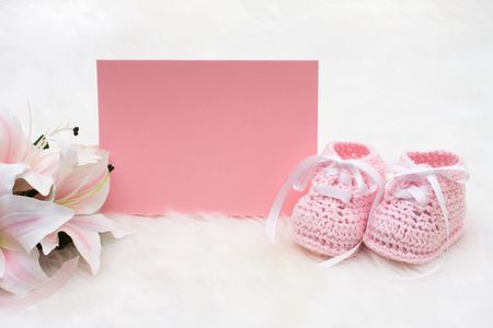 Pink baby booties with a blank card sitting on a white background photo