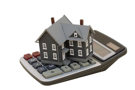 A model house sitting with a calculator on a white background with clipping path, mortgage calculator photo