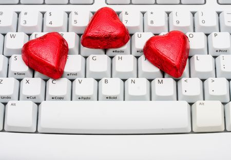 Red foiled chocolate hearts on a computer keyboard, online dating