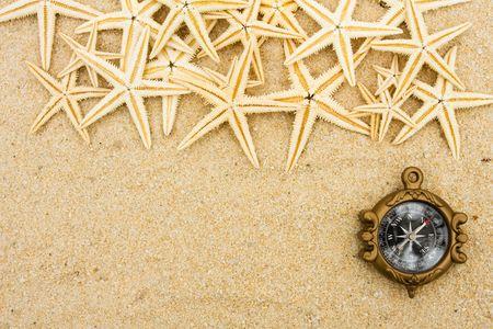 Veel van starfish zitten met een kompas op een zand achtergrond, grens van de vakantie