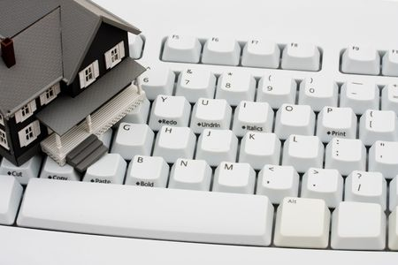 online: A model house sitting on a computer keyboard, online real estate