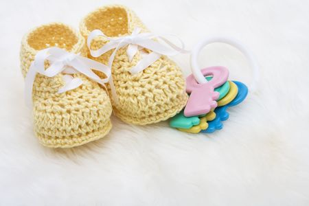 Yellow baby booties with toy keys on a white background