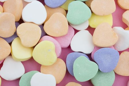 Multi color candy hearts on a pink background Imagens