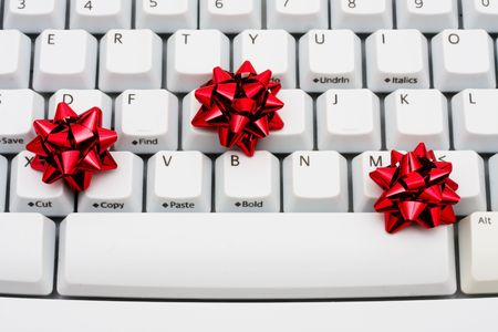 Three red ribbon bows on a computer keyboard, online shopping photo