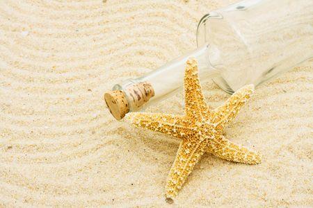 Een lege fles met een zeester in het zand, vakantie Stockfoto