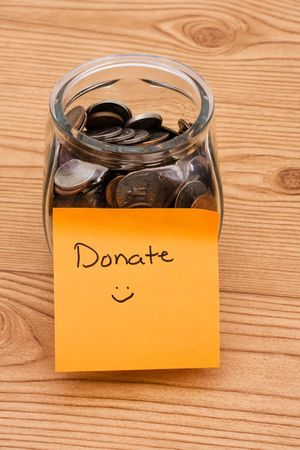A jar full of change sitting on a wooden background, Please help by donating money Stock Photo