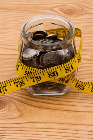 A jar full of change sitting on a wooden background, Calculating your savings photo