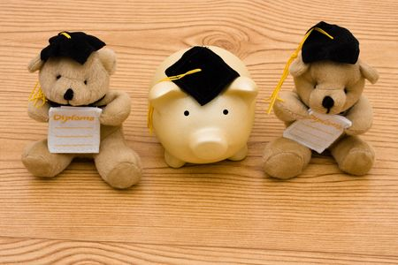 A teddy bears wearing a graduation cap with a diploma on a wooden background, education savings photo