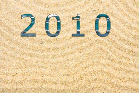 Met veel lijnen die met 2010 geschreven met water, beach achtergrond getekend in het zand
