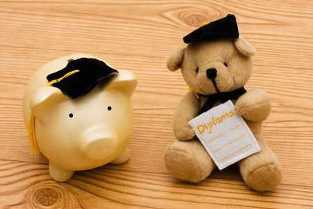 A piggy bank and a bear wearing graduation caps on a wooden background, education savings Banque d'images