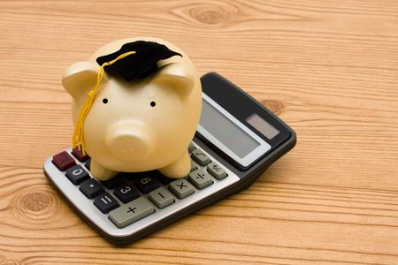 A piggy bank wearing a graduation cap with a calculator on a wooden background, education savings Stock Photo - 6477871