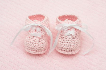 Baby booties on a pink background, baby booties Stock Photo