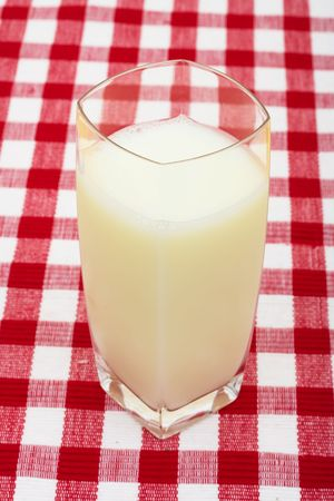 A glass of milk on a red check tablecloth background, a glass of milk