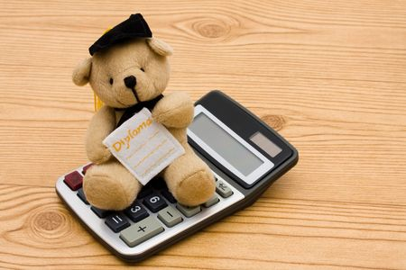 A bear wearing a graduation cap with a calculator on a wooden background, education savings Stock Photo - 6477831