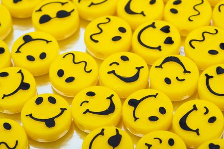 Lots of yellow smiley faces on shiny background, happy days photo